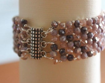 Bangle of beads and crystals in shades of pink and purple