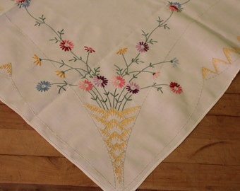 Vintage hand embroidered tablecloth baskets in each corner filled with flowers