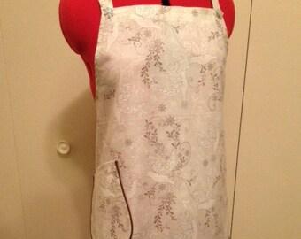 "A ""White Christmas"" full apron. Simple silver sparkle dove design. Brown cord trim. Monogram extra SML"