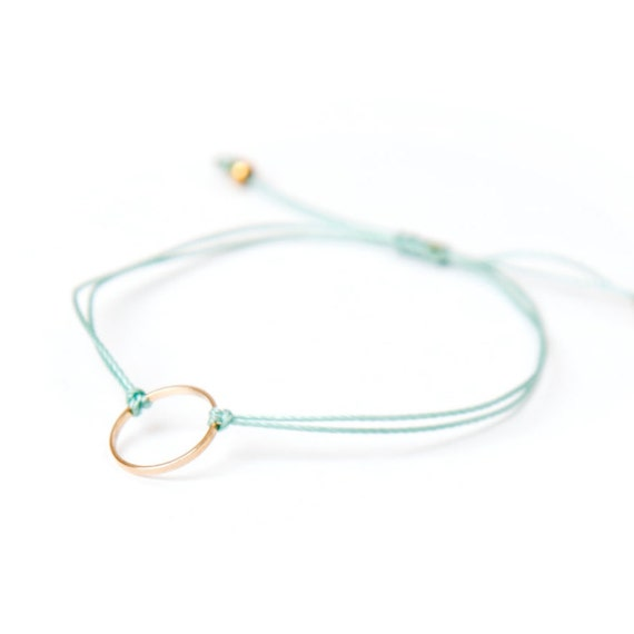 Delicate gold ring bracelet on a nylon thread handmade in Montreal