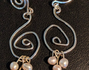 Squiggle earrings with pink pearl droplets.