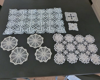 A collection of vintage ecru or cream hand crocheted French mats. Vintage decorative linen and lace.