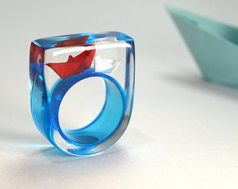 Ship ahoy – maritime boat ring with hand-made folded mini boats made of red and white paper on a blue ring made of resin