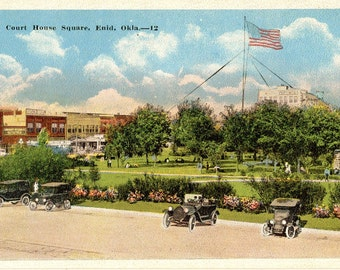 Enid, Oklahoma - Old Cars parked by the square near the Court House, with large American Flag  - Vintage Postcard