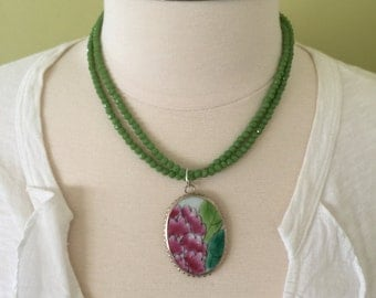 "Summer statement double strand of green faceted glass beads with colorful floral design porcelain pendent, 20"" length."