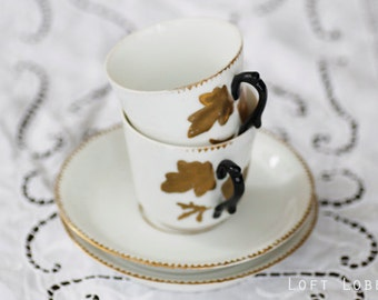 2 vintage thin porcelain teacups and saucers with goldgilt decorations and chic black handles, marked by engraving, unknown maker.