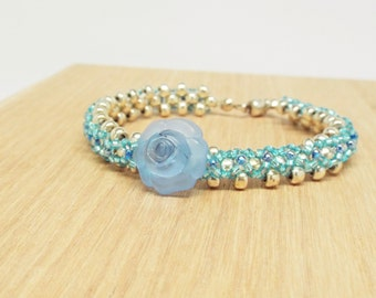 blue and silver seed bead bracelet with acrylic blue rose button centerpiece