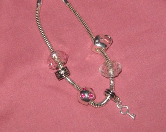 Pink beaded style bracelet with lock and key.
