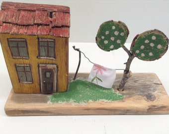 173 -little wood house, yellow with tree and laundry line. red wooden roof yellow exterior, mounted on rustic wood base.