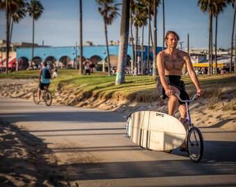Venice Beach Bike Rider along Venice Boardwalk with Surfboard