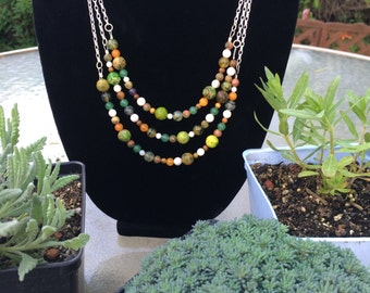 Handmade multi strand necklace with green, white, and orange beads.