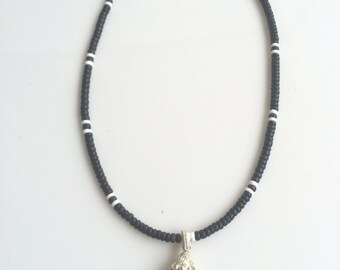 Hand crafted wood beaded necklace with glass pendant.