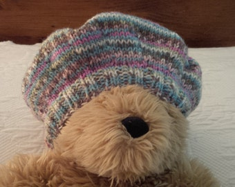 Hat set features tam style hat, thumbless mittens on a string and matching socks