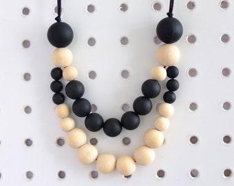 Alison symmetrical teething necklace, black silicone BPA free beads, untreated wood. Sensory,fiddling, breastfeeding, babywearing.