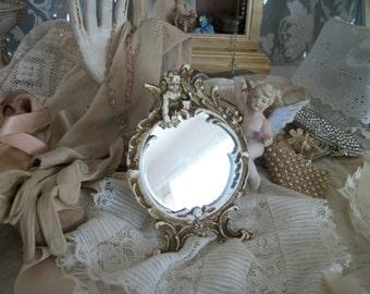 vintage heavy iron ornate cherub frame with mirror, original rustic creamy finish, timeworn patina. small round vanity mirror on easel stand