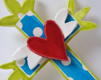 whimsical ceramic cross with winged heart bright blue & chartreuse, polkadots