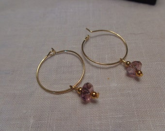 Gold hoop earrings with purple crystal drop