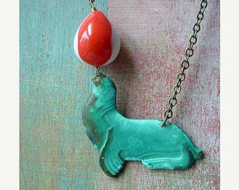 October Sale Sea Lion Pendant Circus Act Necklace   Turquoise Patina Brass with Vintage Lucite Orange White Balancing Ball