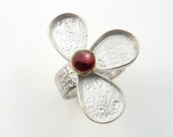 Half sterling silver flower ring set with a cabochon stone in solid gold.Matching earrings and pendant.
