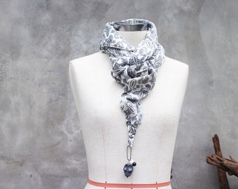 Black and white paisley cotton weighted scarf with large black howlite skull charm