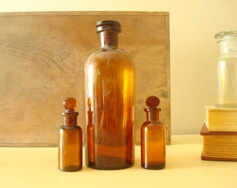 Antique apothecary jars, amber brown, round-top ground glass stoppers, authentic 1900s pharmacy bottles, scientific industrial collectibles