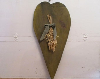Large primitive wood heart wall hanging. Wheat stalks, black & white cloth rag strip, mustard brown green tone. Prim country folk art.