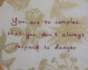 "Hand-stitched Jenny Holzer quote - ""you are so complex you don't always respond to danger"""