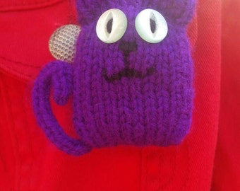 Purple Sausage Cat knitted brooch.