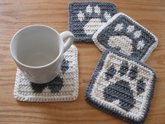 Free Crochet Pattern For Paw Print : Paw Print Coasters. Gray and white crochet coaster set with