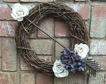 Grapevine wreath with arrow/burlap/floral details