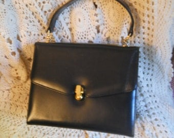 Elite purse pocketbook measures 9 x 7 navy with gold latch which is unique