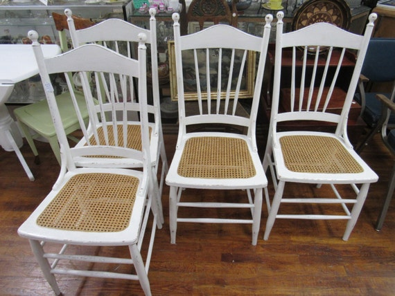 Four white chairs with rattan seats