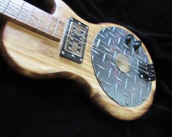 Diamond plate electric three string guitar.