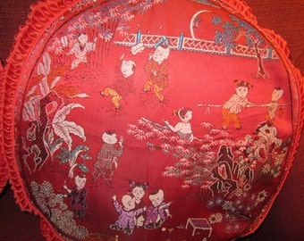 A pair of red round pillow cases, in the Asian style, embroidered in lots of colours, 18 inches diameter, ruched double border, zip closure