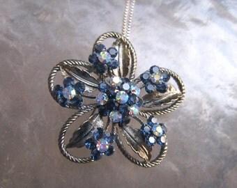 Gorgeous detailed openwork flower pendant necklace with midnight blue and Aurora Borealis rhinestones.