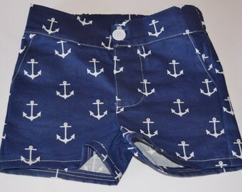 Anchors away! Navy blue infant and toddler shorts featuring a button fly and elastic in the waistband. Navy with a fun nautical print.