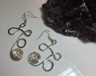 Silver non-tarnish wire earrings with three loops and a big tight spiral on the bottom  hanging on sterling silver french hook earwires.