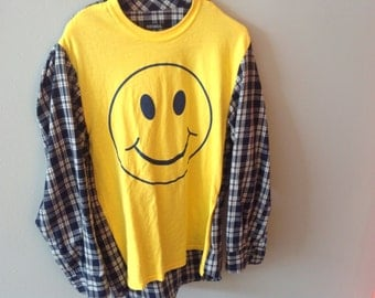 Smiley face emoji with vintage flannel sleeves