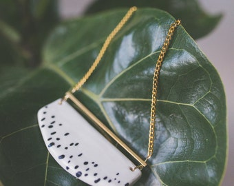Black and white porcelain necklace with a brass bar