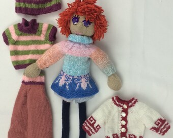Red-haired knitted doll with extra clothes