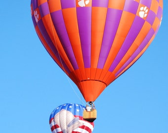 Photograph of Clemson and The Constitution hot air balloons Flying in Blue Skies