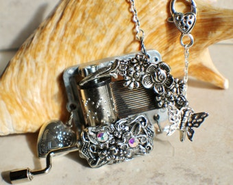 Hand crank music box pendant, music box movement adorned with flowers and butterfly.