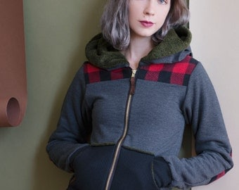 The Fargo Hoodie in grey with red plaid accents. Faux fur lined hood, thumbhole cuffs, and pockets. Zip front with vegan leather accents.