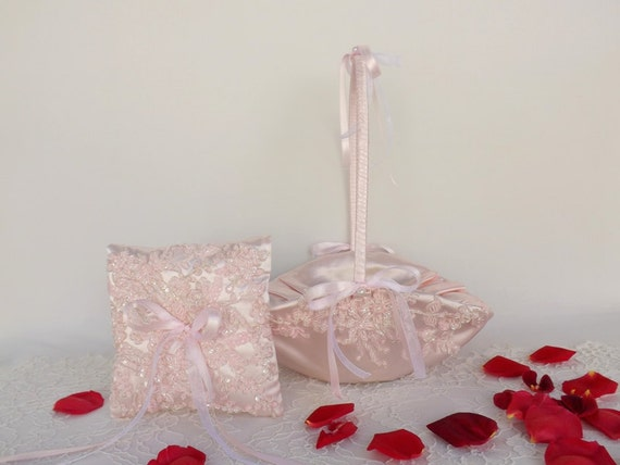 Light pink flower girl basket and wedding ring pillow decorated with beaded lace embroidery.