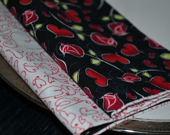 Set of 4 reversible cloth napkins showcasing roses and hearts.