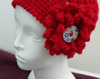 Red childs crochet granny style hat with crochet flower on side and decorative button.Age approx 3-5years