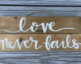 """Hand-painted """"love never fails"""" wood sign"""