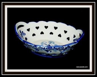 Decorative basket made of ceramics in delft blue painted dutch pattern.
