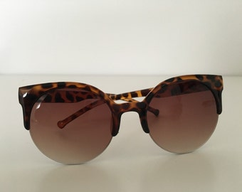 Sunglasses, semi rim sunglasses, cat eye sunglasses in brown and black.