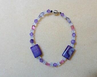 Purple beads primarily make up this fun, casual bracelet.  #B 0016-15.